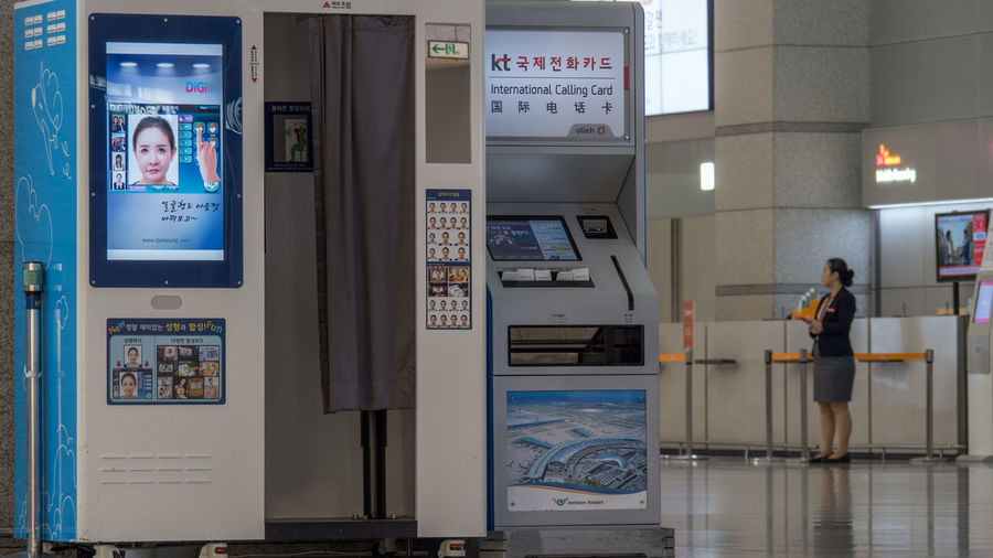 SEOUL, SOUTH KOREA - OCTOBER 22, 2015: International Calling Card machine next to photo booth in the airport of Incheon Airport Automat Booth Call Card Communication Hall Horizontal Incheon Incheon International Airport Instant Kiosk Machine Person Photo Seoul Service Shot South Korea Technology