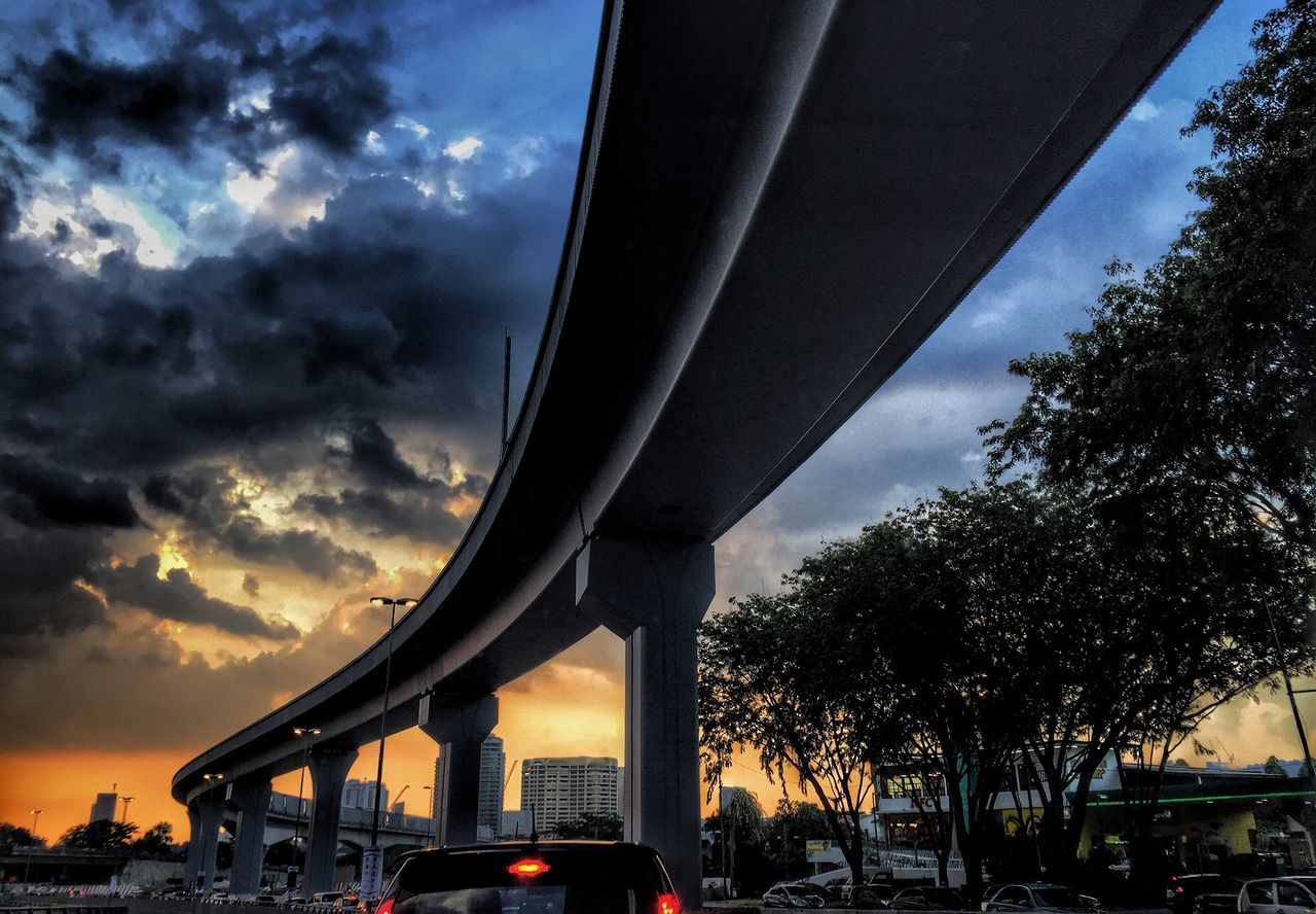 Low Angle View Of Bridge Over Street Against Sky At Dusk