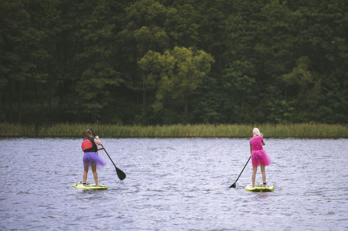 Activyti girls and a paddle Chilling A Paddle Childhood Chill Females For Love Girls Irritations Lake Leisure Activity Nature Paddleboarding People Plant Real People Rear View Sport Tree Two People Water Waterfront Women Adventures In The City Summer Sports