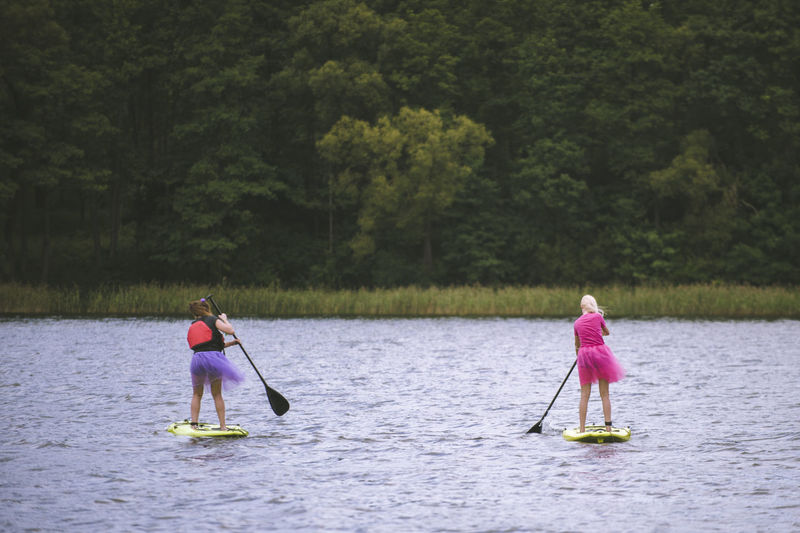 Activyti girls and a paddle Chilling A Paddle Childhood Chill Females For Love Girls Irritations Lake Leisure Activity Nature Paddleboarding People Plant Real People Rear View Sport Tree Two People Water Waterfront Women Adventures In The City