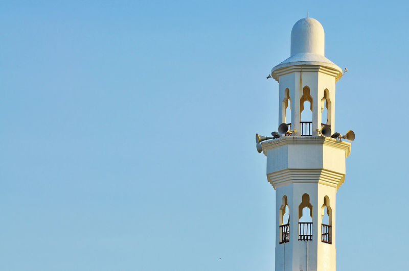 Low angle view of megaphones on minaret against clear blue sky