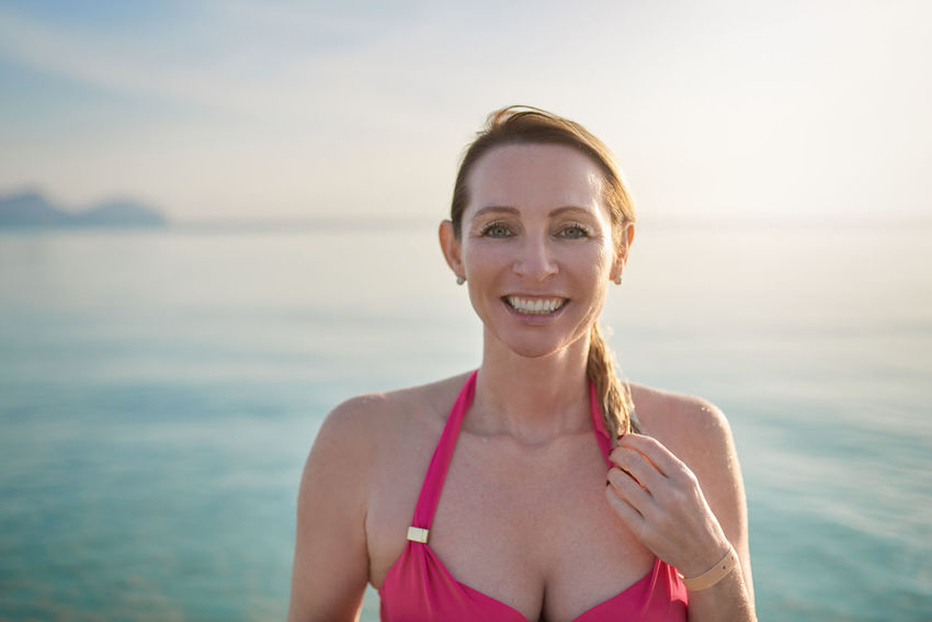 Smiling attractive woman standing at the beach Copy Space Happy Looking At Camera Sunlight Sunny Travel Woman Beach Best Ager Bikini Body Conscious Copyspace Middle-aged Ocean Resort Smiling Tropical Vacation Water