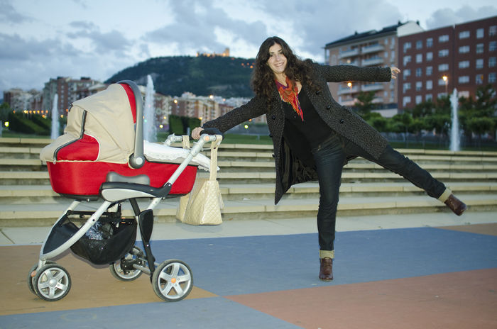 Baby carriage and happy mother in city park Architecture Baby Baby Carriage Babycar City Daughter Day Full Length Happy Happy People Jaén Jump Leisure Activity Lifestyles Mother Mothernature One Person Outdoors Park Real People Smiling Transportation Women Young Adult Young Women