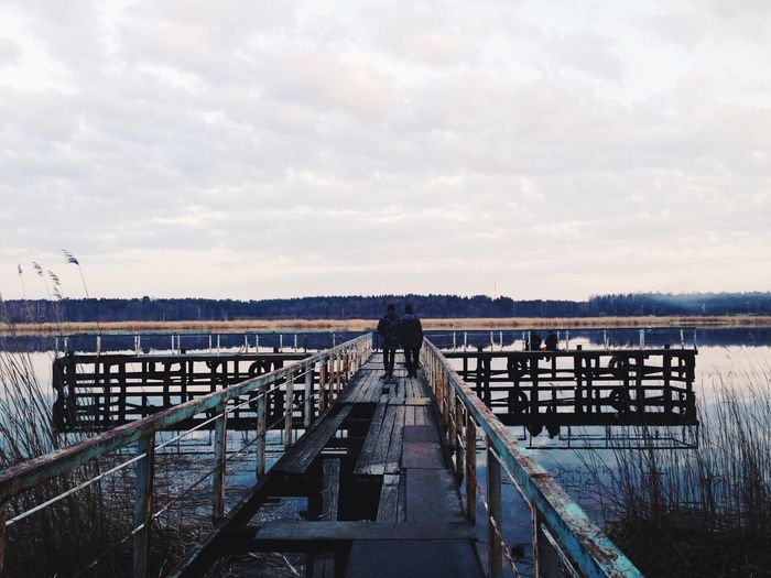 Rear view of people walking on pier over river