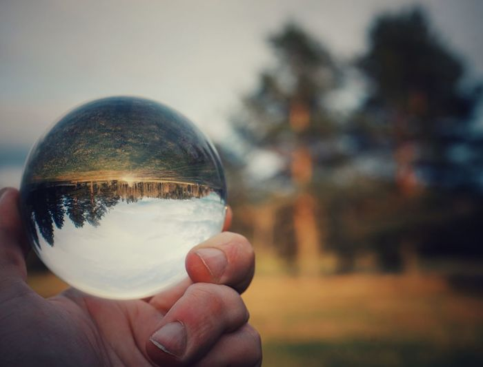 Close-up of hand holding crystal ball against blurred background