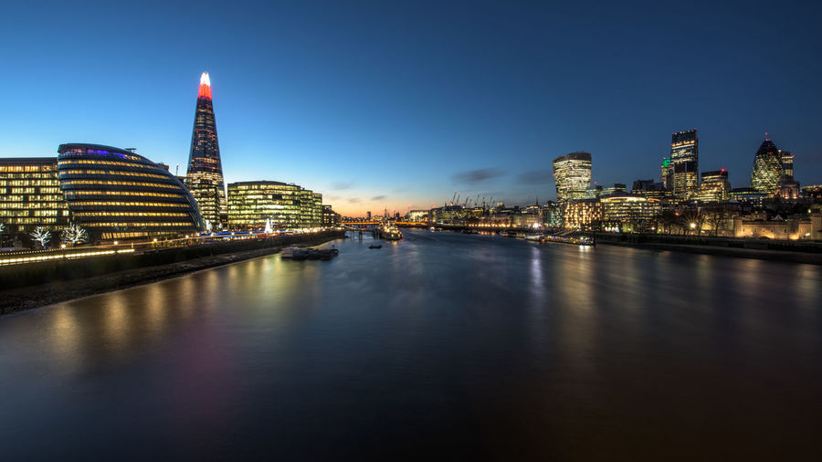 Thames River Amidst Illuminated Buildings In City