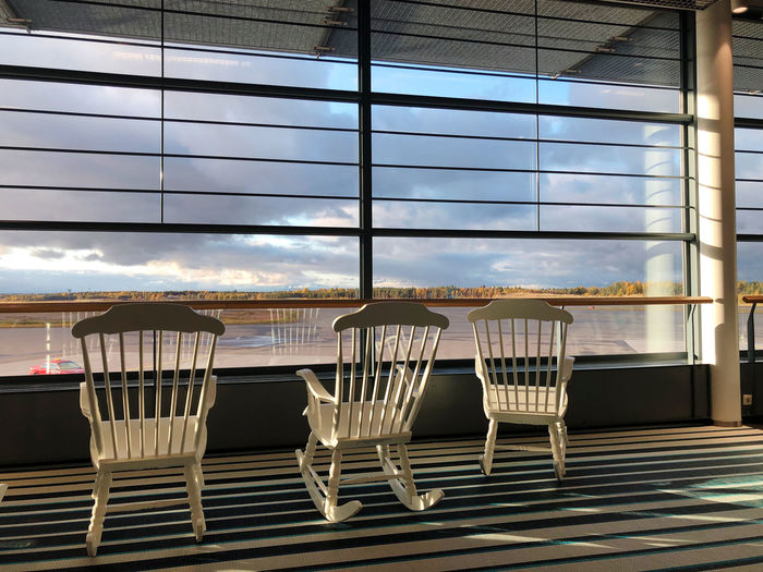 Empty chairs and tables against sky seen through glass window