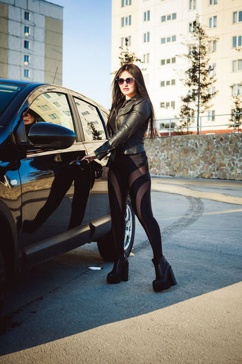 Full Length Of Fashionable Woman Opening Car Door