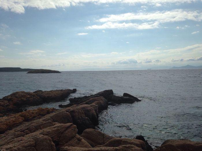 Rocks in sea against cloudy sky