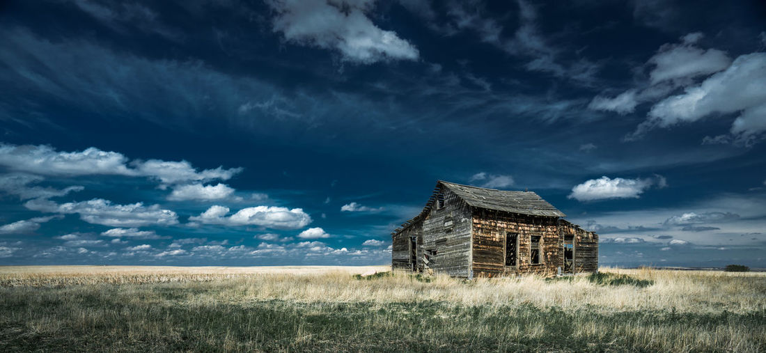 Abandoned house on land against sky
