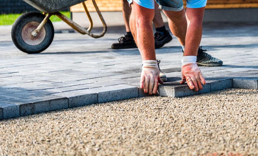 Construction worker arranging paving stones on street