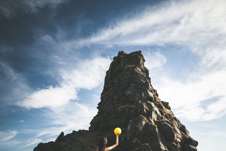 Low Angle View Of Woman Holding Ball By Rock Formation Against Sky