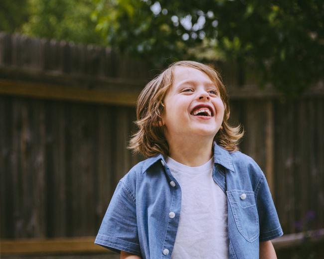Cute boy laughing in back yard