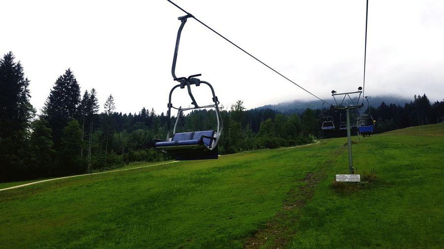 Overhead cable car on field against sky