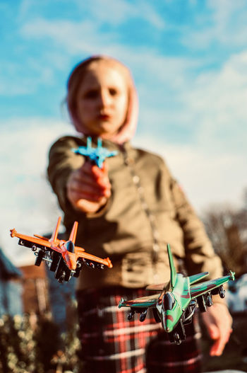 Low angle view of boy playing with airplanes against sky