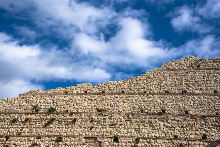 Low angle view of wall against cloudy sky