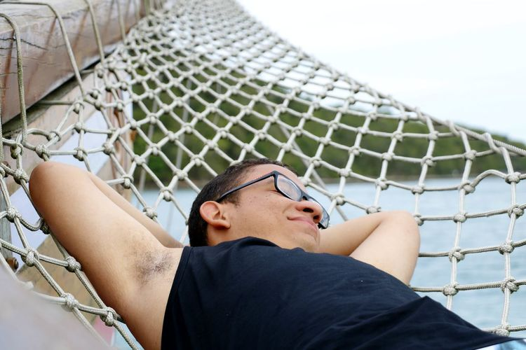 Close-Up Of Man Relaxing On Hammock Against Sea