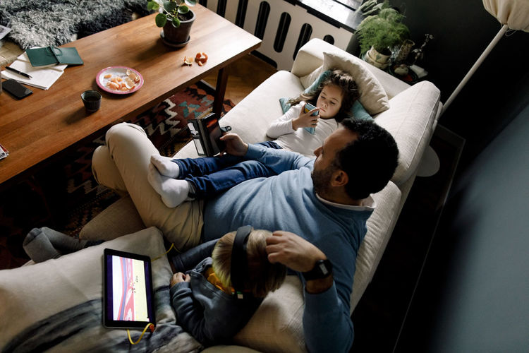 High angle view of people using mobile phone at home