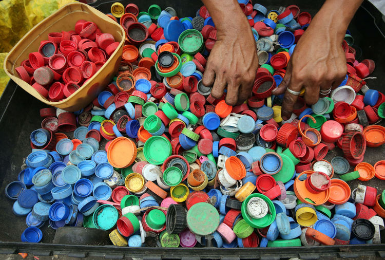 Cropped hands with colorful bottle caps in container