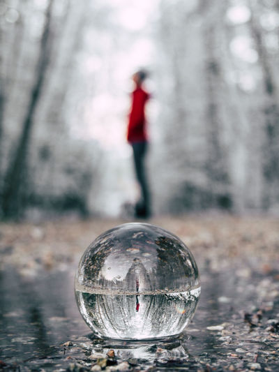Reflection of man on crystal ball in forest