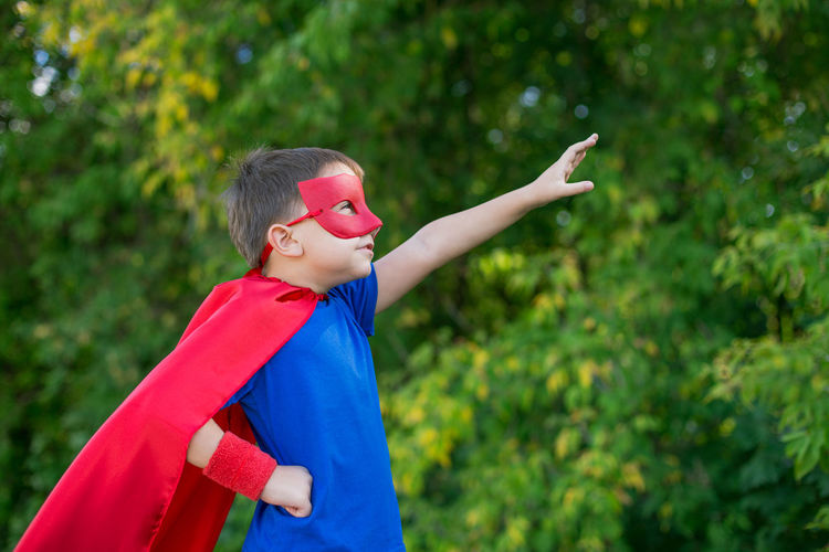 Boy in superman costume standing against tree