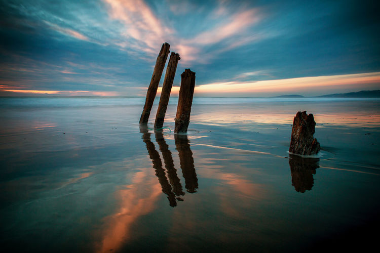 Sky Water Cloud - Sky Sea Reflection Tranquility Beauty In Nature Tranquil Scene Nature No People Scenics - Nature Horizon Waterfront Sunset Horizon Over Water Wood - Material Post Wooden Post Land