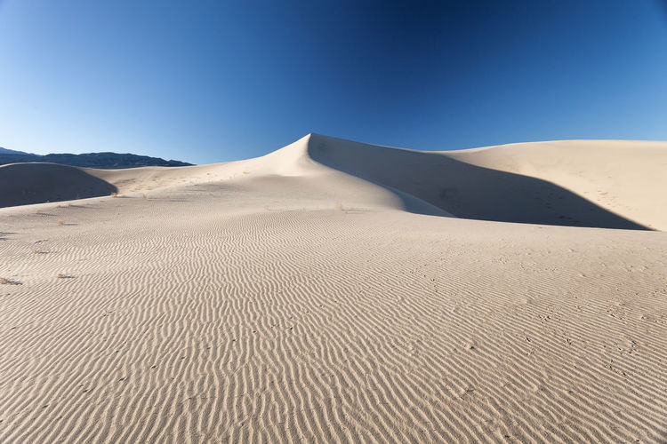 Sand dunes against clear blue sky