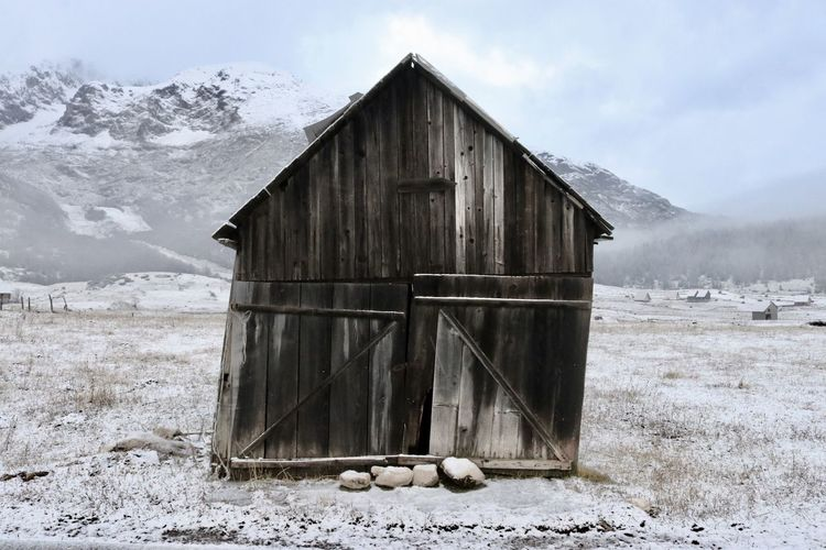 Abandoned house on field during winter
