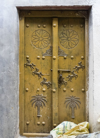 ancient traditional iron doors in Oman Ancient Door Entrance Oman Ancient Architecture Arabic Symbols Close-up Closed Door Desert Architecture Door Door Decor Door Designs Door Details Iron Doors No People Omani Sybmols Safety Sut Down Traditional Architecture