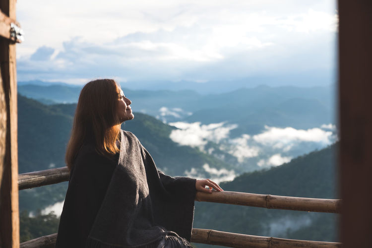 Smiling woman standing by railing in balcony against mountains