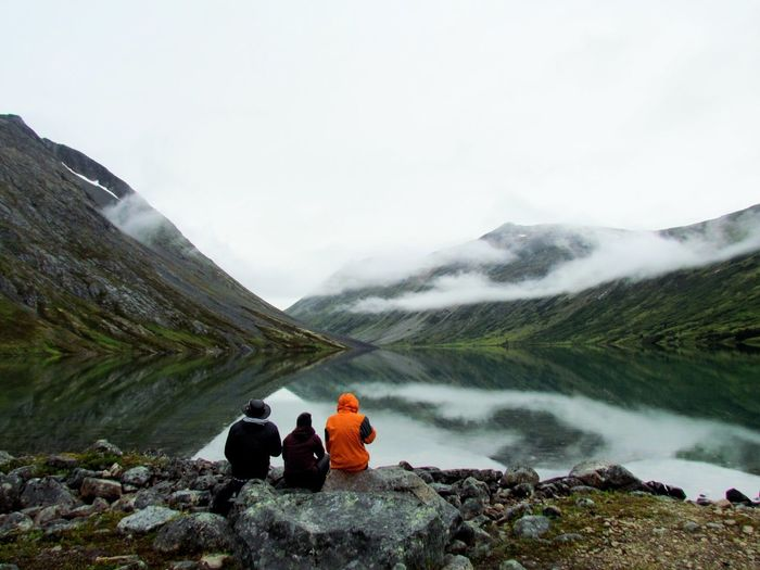 Rear view of people sitting on mountain by lake against sky