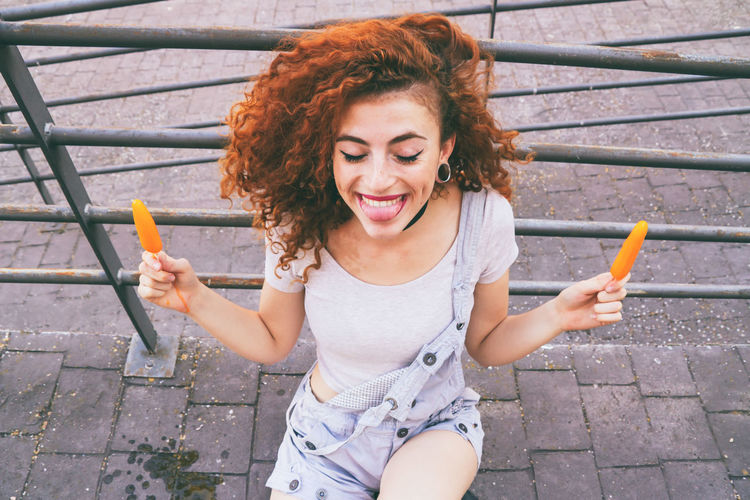 Young happy woman holding two ice creams Afro Funny Happiness Happy People Redhead Summertime Youth Of Today Adult Curly Curly Hair Cute Day Enjoying Life Ice Cream Lifestyles One Person Outdoors Pretty Real People Redhead Smile Smiling Summer Summer Vibes Young Adult