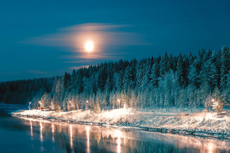Scenic view of lake against sky at night during winter