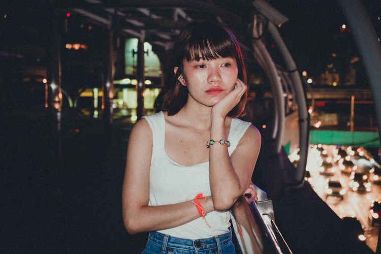 Thoughtful young woman standing in footbridge at night