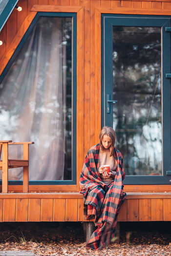 Full length of woman sitting against house