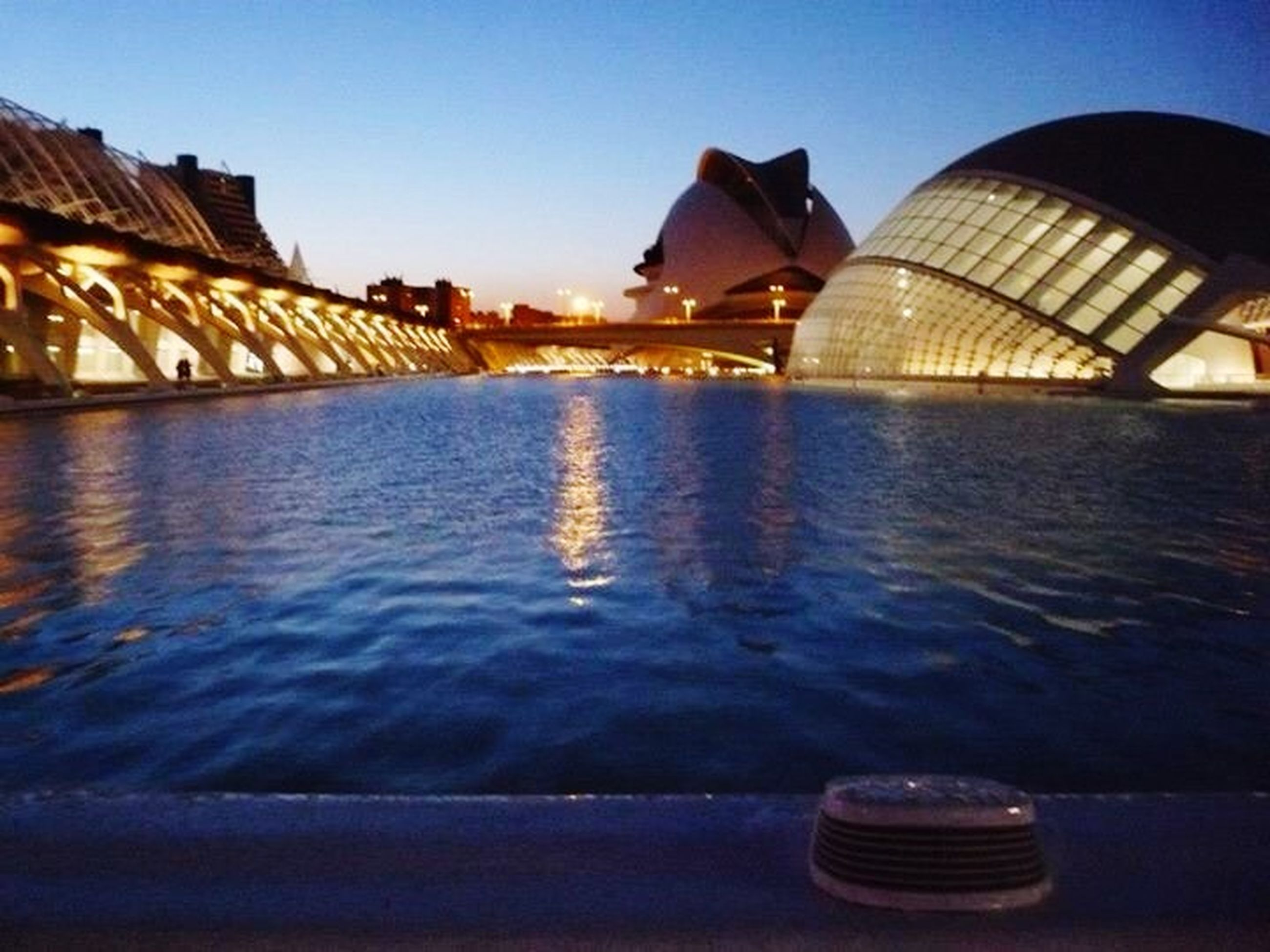 water, architecture, built structure, reflection, waterfront, building exterior, illuminated, clear sky, river, blue, city, transportation, travel destinations, sky, famous place, rippled, outdoors, tourism, travel, bridge - man made structure