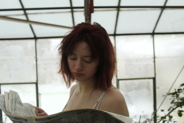 Young woman reading newspaper against window