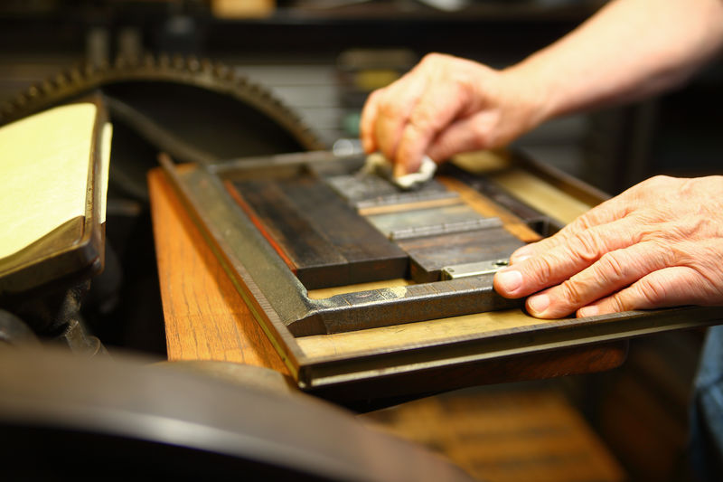 Printer wipes clean block of letterpress type One Person Indoors  Real People Working Preparation  Craft Man Printer Letterpress Printing Metal Type Studio Shot Hands Fingers Wiping Machinery Letterpress Machine Gear Printing Chase Closeup Rag Ambient Light Holding