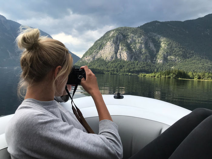 Side View Of Woman Photographing Mountain From Boat In Lake