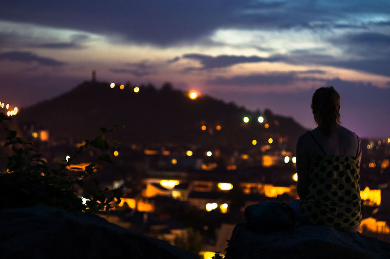 Rear view of woman sitting against illuminated city during sunset