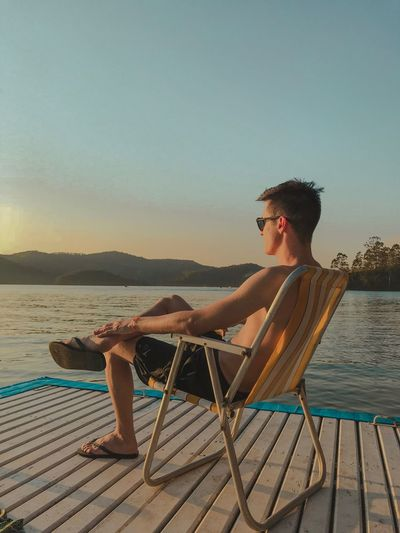 Full length of young man relaxing by sea on chair