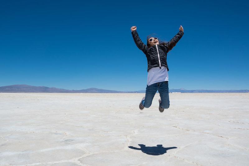 Girl jumping at salinas grandes against blue sky