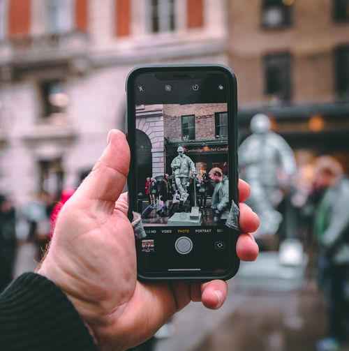 A photo of a phone taking a photo of a street performer and passersby in London, England. LONDON❤ London London lifestyle London Streets Street Performance City Communication Focus On Foreground Hand Human Hand IPhone IPhoneX IPhoneography Iphonephotography Mobile Phone Photographing Photography Themes Smart Phone Street Performer Street Photography Streetphotography Technology