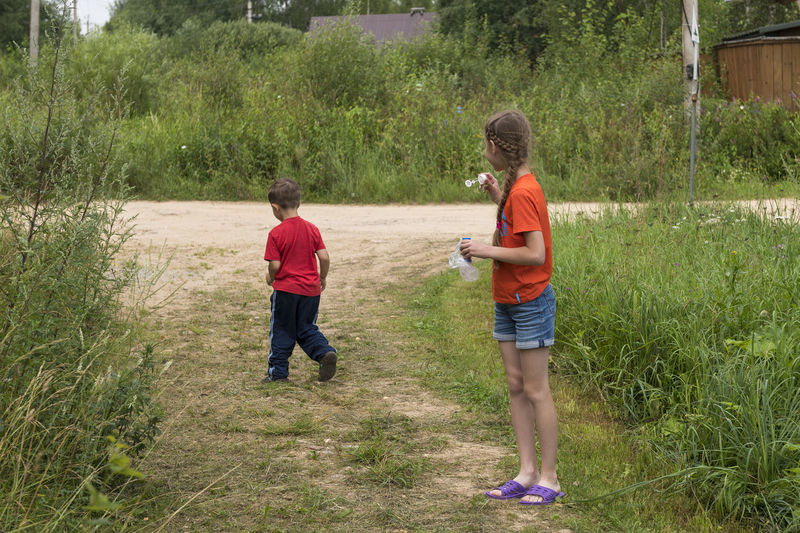 Girl blowing bubbles with boy walking on grass against plants
