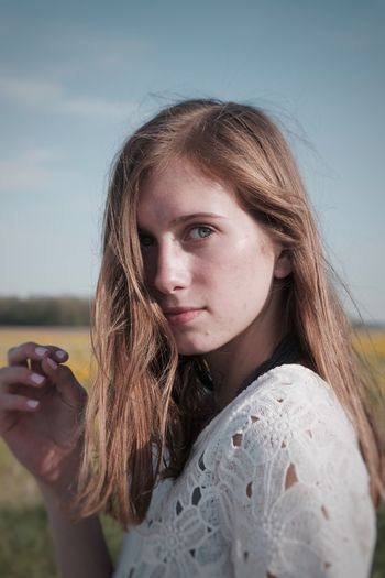 Close-up portrait of young woman against sky