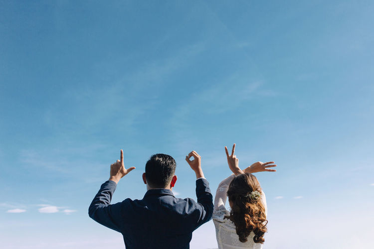 Wedding Couple raised hand up LOVE sign on the blue sky. romantic scene. copy space for quotes Couple Love Romantic Sky And Clouds Wedding Arms Raised Day Gesturing Hand Human Body Part Human Hand Leisure Activity Lifestyles Men Outdoors Peace Sign - Gesture People Real People Rear View Selective Focus Sky Togetherness Women