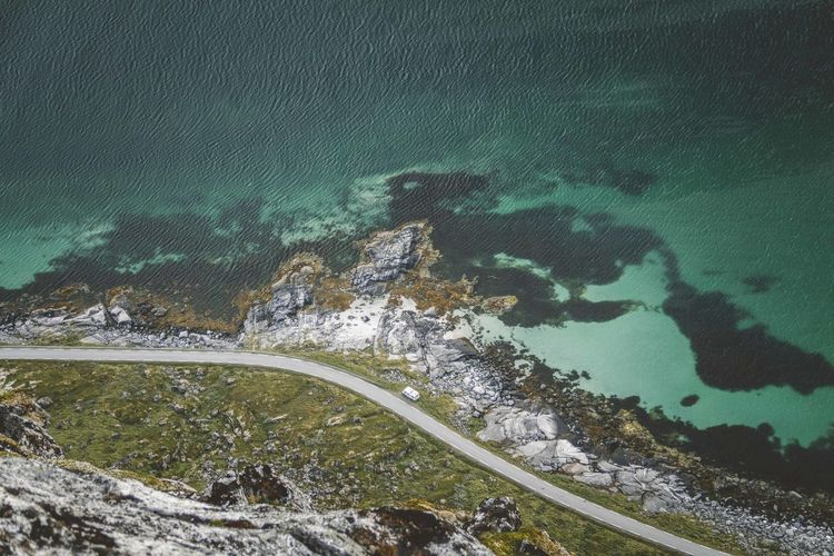 Aerial view of land by sea