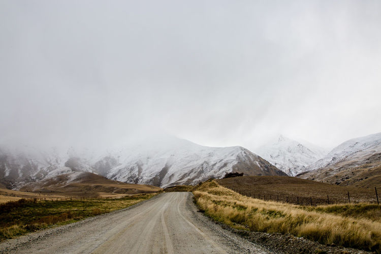 Country road leading towards snowcapped mountains against sky
