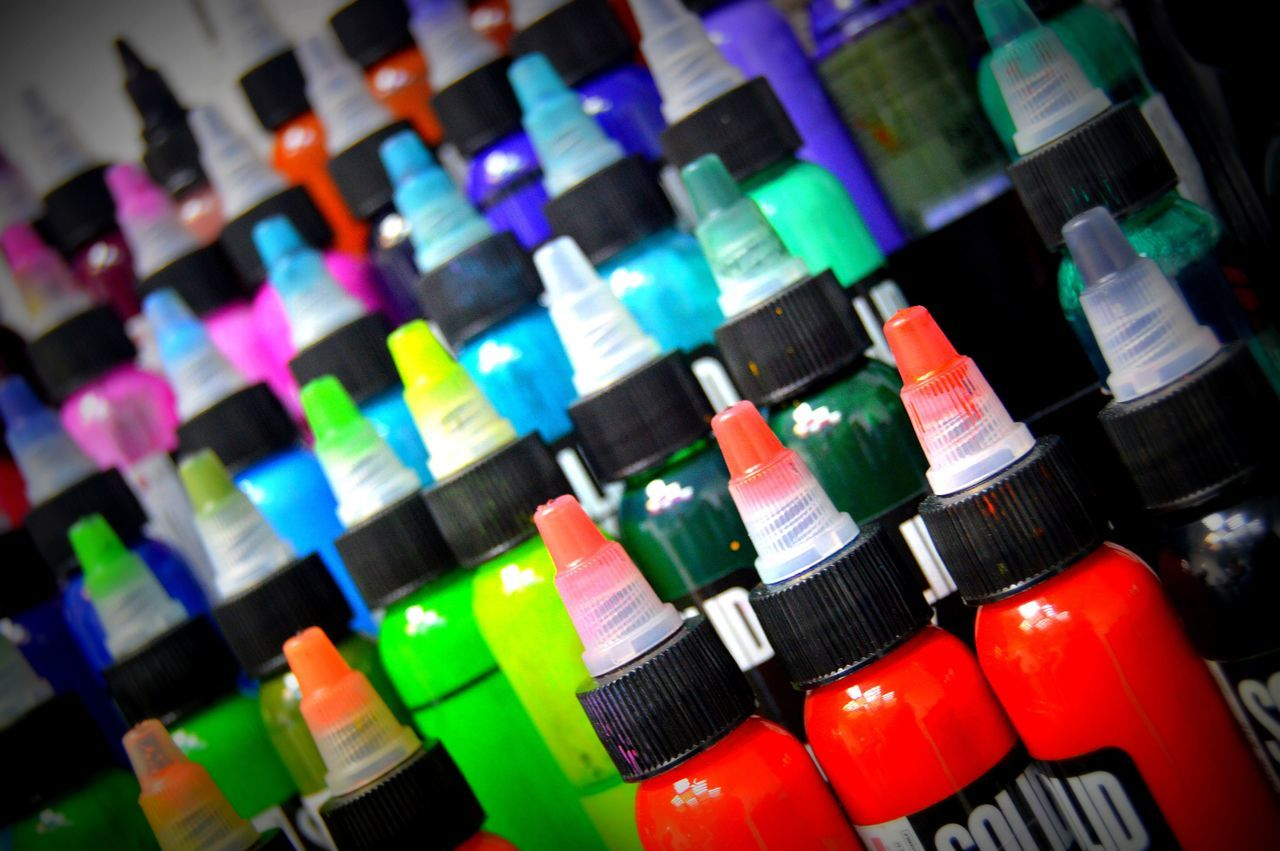HIGH ANGLE VIEW OF MULTI COLORED BOTTLES ON SHELF