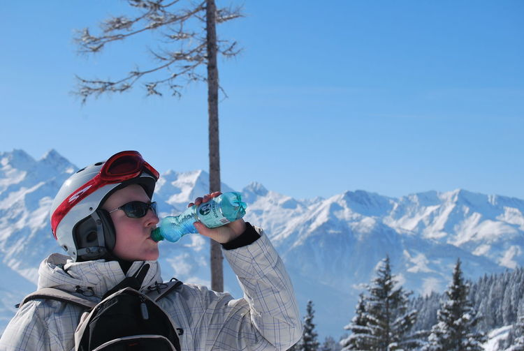Woman Wearing Skiing Helmet Drinking Water Against Snowcapped Mountain